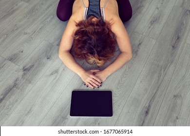 high angle view of a young woman alone following yoga class at home using a tablet