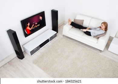 High Angle View Of Young Woman Lying On Couch Watching Movie