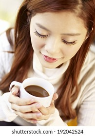 high angle view of young woman holding coffee cup, focus on lip.