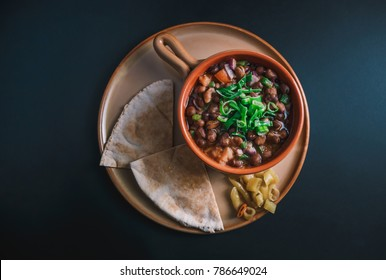 A high angle view/color studio image of Egyptian, Arabian, Middle Eastern Traditional food (Fava Beans with Vegetables/Green Paprika) A.K.A (Foul) - Also served in Lebanon and most of Arabian countrie