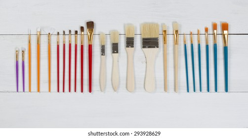 High angled view of brand new paint brushes organized on white wood. Layout in horizontal format.