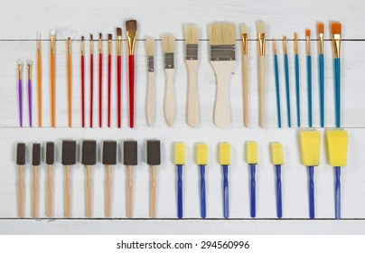 High angled view of brand new paint brushes and applicators organized on white wood. Layout in horizontal format.