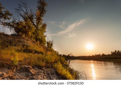 The high bank of the river at sunset