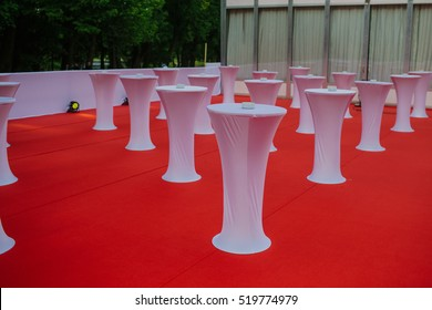 High bar tables covered with white cloth stand over the red floor