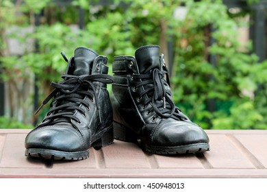 The high black leather boots out door background,