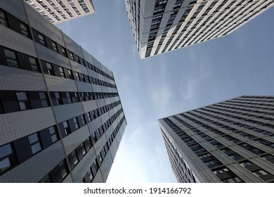 High bottom up perspective view of modern city tower buildings with many windows in the urban cluster