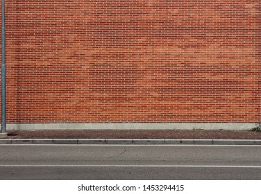 High brick wall with a porphyry sidewalk and an asphalt street in front. Urban background for copy space