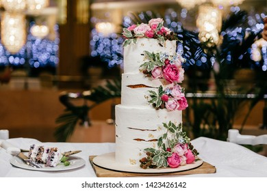 High cake with white mastic, decorated at each level with pink peonies and leaves  on white substrate on table next plate with cut piece. Wedding cake decorated with flowers. dessert on festive table