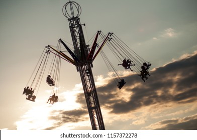 high carousel attraction with people silhouettes on sunset background