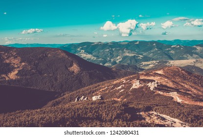 High Carpathian mountains under vibrant blue sky with white clods.Beautiful mountain landscape in autumn.Instagram vintage film filter with unussual colors