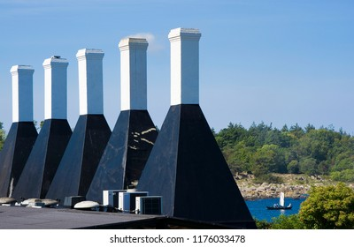 High chimneys of Svaneke smokehouse known as the Five Sisters, Bornholm, Denmark. Fishing boat in the background.