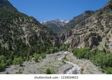 High cliff walls border a rushing river in the wilderness backcountry of the American west.