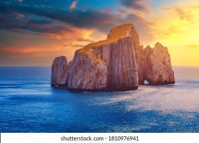 "High cliffs of Mediterranean coast, ""Pan di Zucchero"" stack rock in Masua, west coast of Sardinia, Italy. Concali su terrainu a limestone formation in southern Sardinia, Italy."