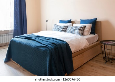 High comfortable prepared bed with plenty of pillows and blue cover