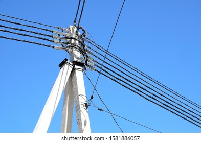 High concrete pole with lots of electrical wires.