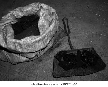 High contrast black and white photograph of coal in a sack and shovel on dirty wooden floor