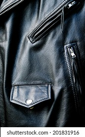 High contrast close up of black leather biker jacket showing zippered pockets and coin pocket with snap button and portion of belt in sunshine.