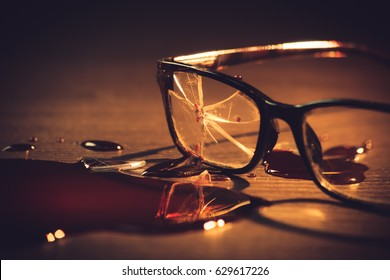 High contrast image of broken glasses on the floor with blood
