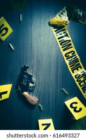 High contrast image of a crime scene with gun and markers on the floor
