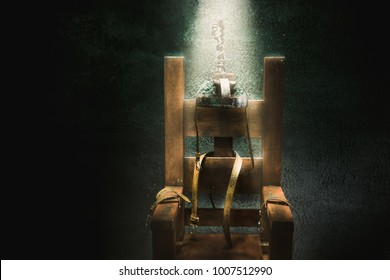 High contrast image of an electric chair scale model on a dark backgorund with light rays