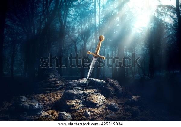 Imagen de alto contraste de Excalibur, espada en la piedra con rayos claros y motas de polvo en un bosque oscuro