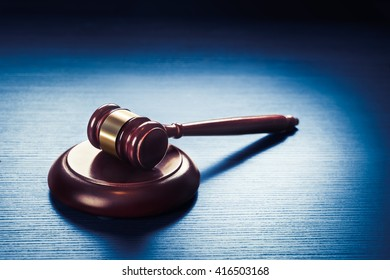 high contrast image of Judge's gavel on a blue wooden background
