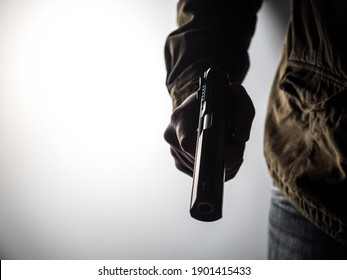 High contrast image of a man holding a gun against a brightly lit background