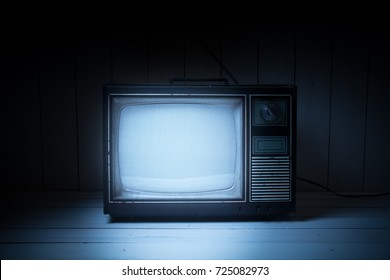 High contrast image of an old vintage TV with white noise on white wood.