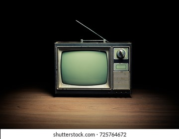 High contrast image of an old vintage TV on white wood.