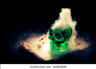 High contrast image of a potion bottle shaped like a skull with smoke