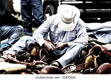 High contrast image of a rodeo cowboy behind the scenes working on his saddle.