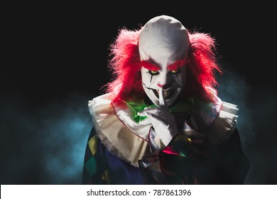 High contrast image of a scary clown on a black background