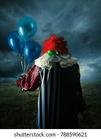 High contrast image of a scary clown with blue balloons on a field