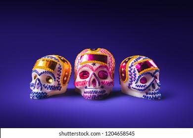 "High contrast image of sugar skulls used for ""dia de los muertos"" celebration in a purple background"