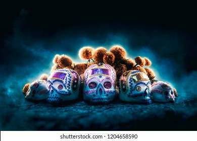 "High contrast image of sugar skulls used for ""dia de los muertos"" celebration in a dark background with cempasuchil flowers"
