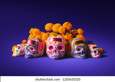 "High contrast image of sugar skulls used for ""dia de los muertos"" celebration in a purple background with cempasuchil flowers"