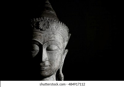 High contrast image of a traditional buddha head against a black background with copy space. The face is serene and showing peaceful meditative contemplation. Mindfulness and meditation image.