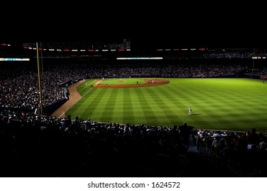 high contrast image of Turner Field at night; the stadium is highlighted in green, with crowd very dark