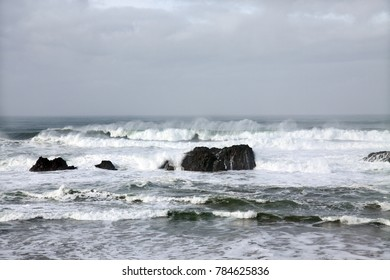 High contrast view of waves crashing on rocks of Oregon beach on a cloudy day