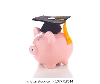 High Cost of Education: A mortarboard on a piggy bank representing the high cost of a college education.