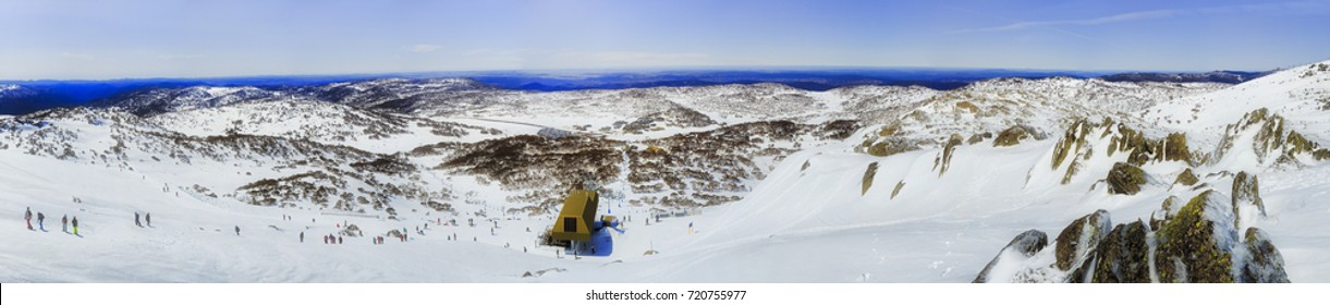 High country of Australian SNowy mountains from top of Back Perisher mount overlooking Perisher valley with chairlift and skiing resort infrastructure and walking people.