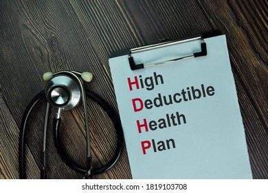 High Deductible Health Plan write on a paperwork isolated on wooden table.
