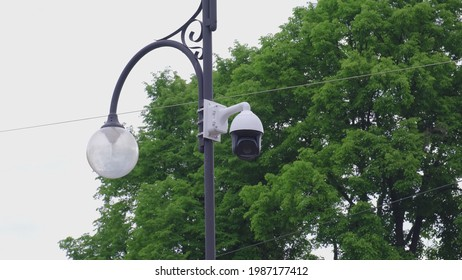 High Definition Rotating Public Surveillance CCTV Security Camera Mounted on a City Lamp Post Performing Area Visual Sweep