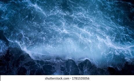 High definition waves crashing against a coastal body of rocks.