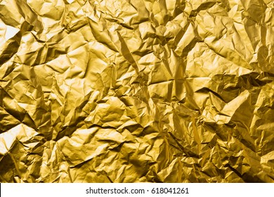 High detailed abstract crumpled gold foil texture.