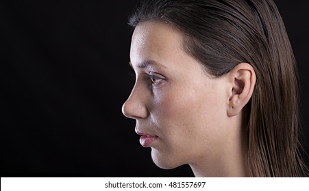 High detailed portrait of young girl face, profile view, wet hair and dazed expression, black background