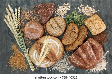 High dietary fiber health food concept with multi seed whole grain rolls, seeds, nuts and cereals on marble background top view. Foods high in omega 3 fatty acids, antioxidants and vitamins.
