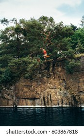 High diver leaping from conifer to the water in a flooded mine. A man captured in the middle of jump - headed down and his legs are crossed. The image also captures several meters altitude of jump.