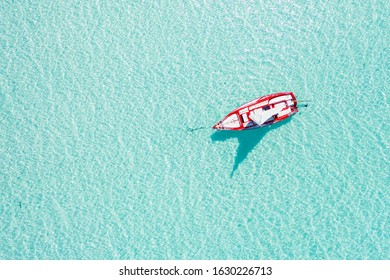 High drone view of a sailing boat in a paradise white sand beach island in the caribbean Bacalar lagoon, Mexico