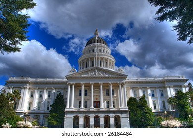 an high dynamic range image of the California State Capital Building from a distance bordered by trees and a blue sky with grey and white clouds